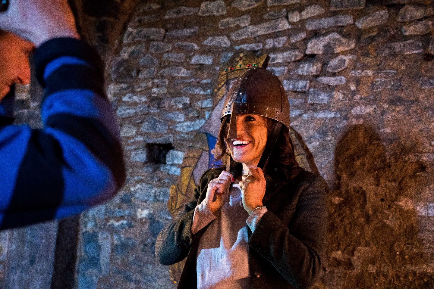 Woman trying on helmet at Newark Castle