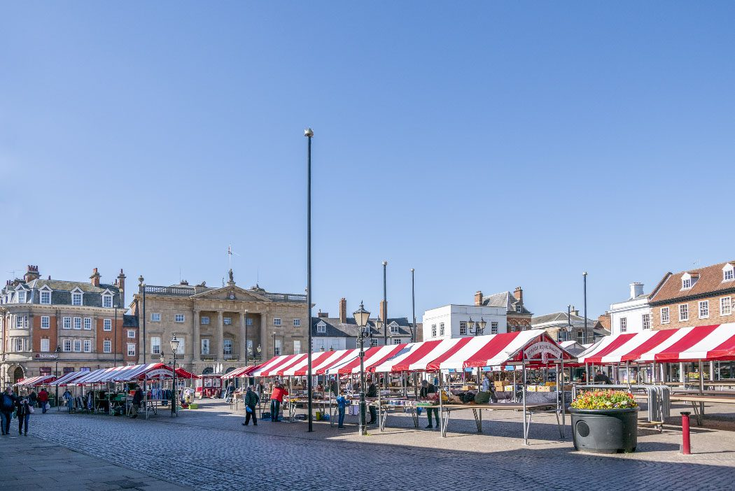 Red and white stalls in Newark Market Place overlooked by the town hall