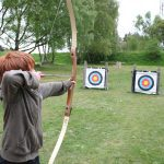 Young child aiming at three archery targets as Walesby Forest
