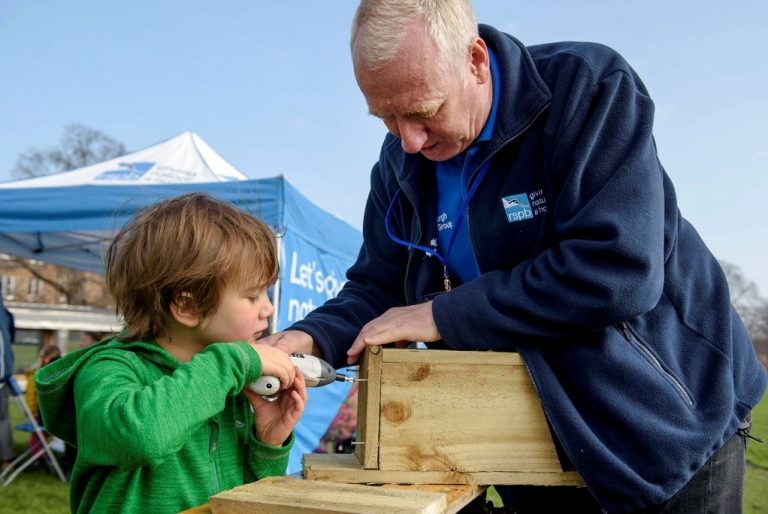 RSPB volunteering helping a young boy build a nest box