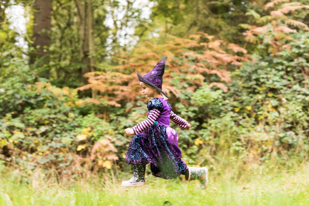 a young girl in a witches costume playing in the forest